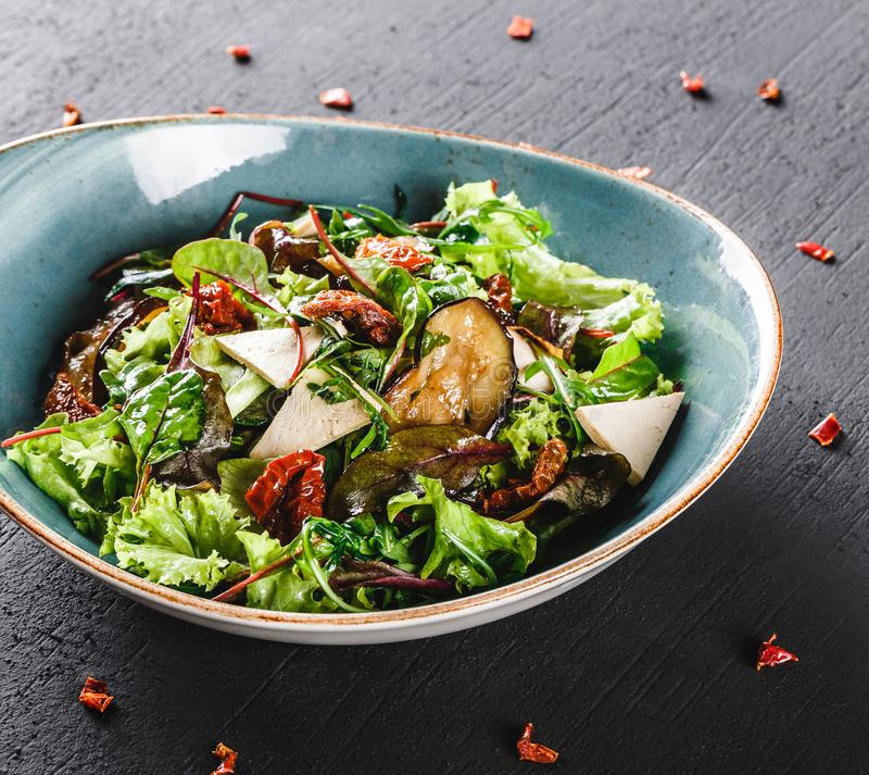 Ensalada sana con la berenjena asada a la parrilla, verdes, arugula, espinaca, lechuga, los tomates secados y el queso en placa s imagen de archivo