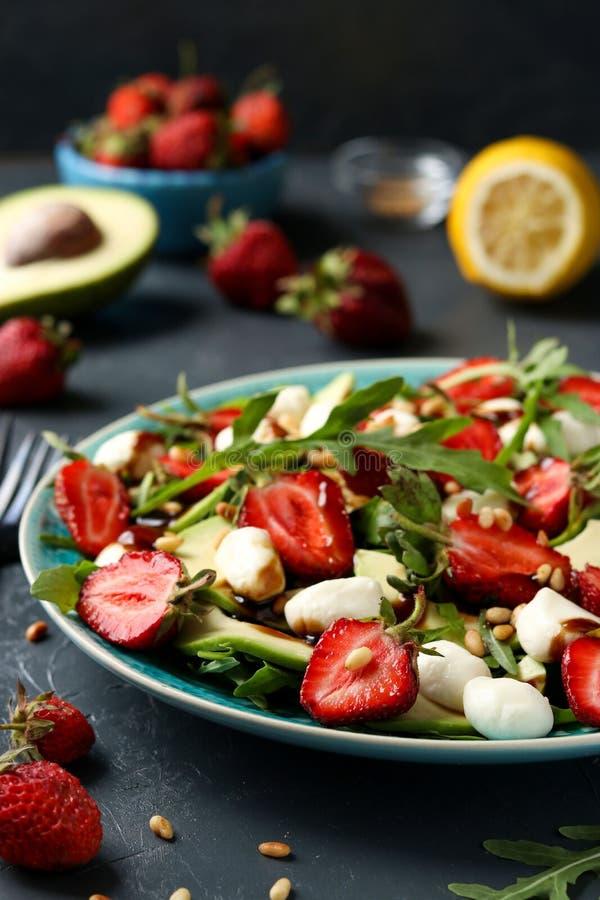 Ensalada sana con las fresas, aguacate, arugula y mozzarella, vestidos con el aceite de oliva y la preparación balsámica localiza imagen de archivo libre de regalías