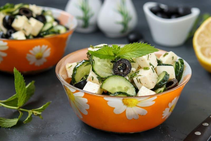 Ensalada sana con los pepinos, queso Feta y aceitunas, con el aceite de oliva y los verdes, situados en cuencos contra un fondo o imágenes de archivo libres de regalías