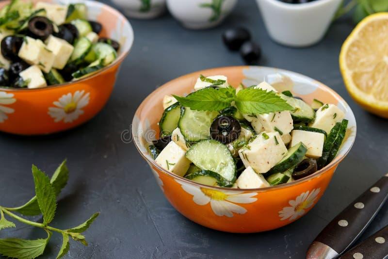 Ensalada sana con los pepinos, queso Feta y aceitunas, con el aceite de oliva y los verdes, situados en cuencos contra un fondo o imagenes de archivo
