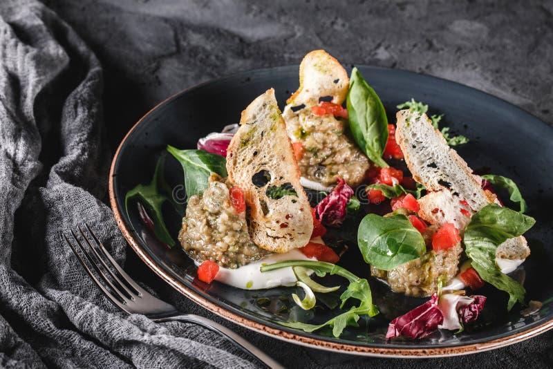 Ensalada sana de la berenjena, del arugula, de la espinaca, del tomate, de cuscurrones y de la salsa asados a la parrilla en una  imagen de archivo