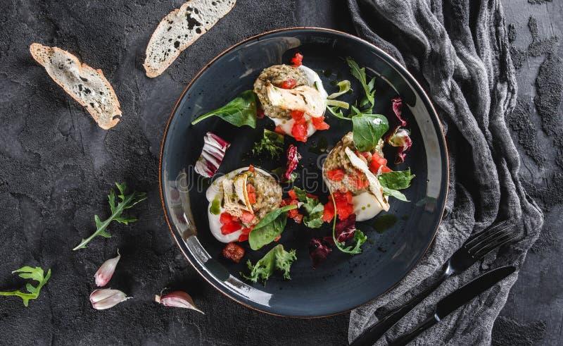 Ensalada sana de la berenjena, del arugula, de la espinaca, del tomate, de cuscurrones y de la salsa asados a la parrilla en una  fotografía de archivo