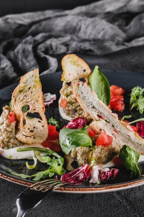 Ensalada sana de la berenjena, del arugula, de la espinaca, del tomate, de cuscurrones y de la salsa asados a la parrilla en una  foto de archivo