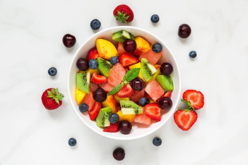 Ensalada sana de la fruta fresca y de la baya con la menta en un cuenco en el fondo de mármol blanco Alimento sano fotografía de archivo libre de regalías