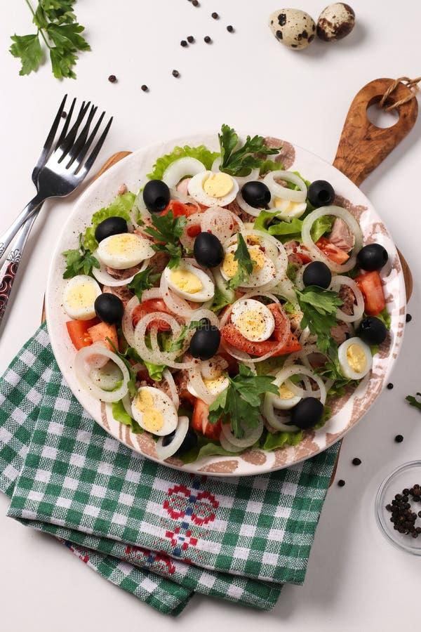 Ensalada sana de la lechuga orgánica con el atún conservado, los tomates, los huevos de codornices, las aceitunas negras y las ce imagenes de archivo