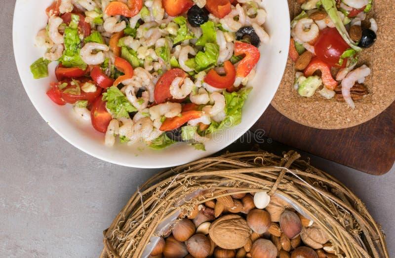 ensalada sana de la proteína con los camarones, tomates, avokado, lechuga, aceite, aceitunas en las galletas de alto valor protei fotografía de archivo