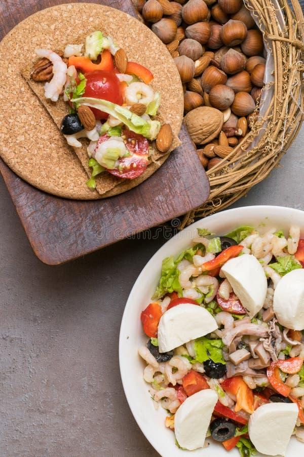 ensalada sana de la proteína con los camarones, tomates, avokado, lechuga, aceite, aceitunas en las galletas de alto valor protei imagen de archivo