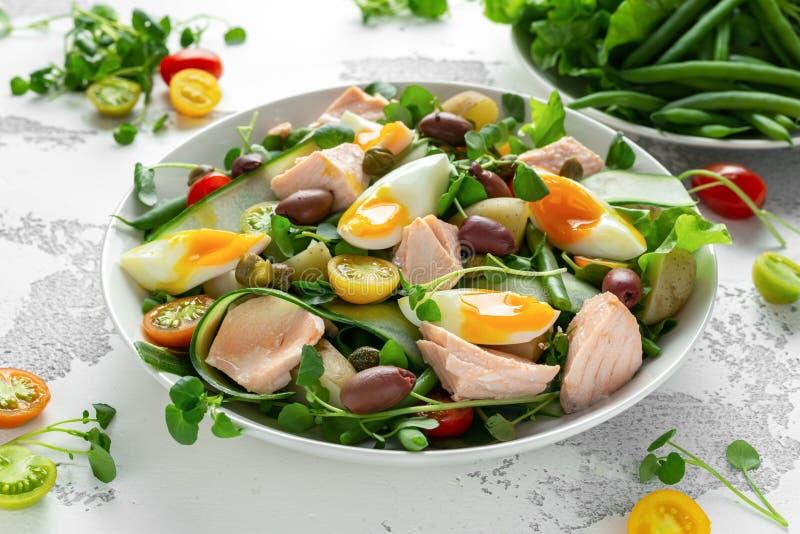 Ensalada sana de Nicoise con los salmones, tomates de cereza dulce coloridos, aceitunas, habas verdes, cintas del pepino, suavida foto de archivo libre de regalías