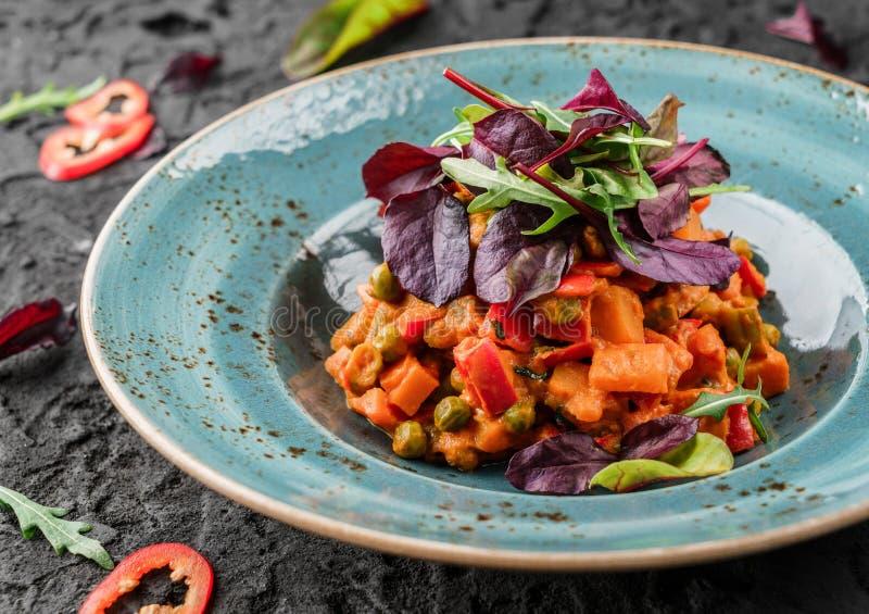 Ensalada sana del curry de la calabaza del vegano con con pimientas y el tomate en placa de cerámica sobre fondo oscuro Comida sa foto de archivo libre de regalías