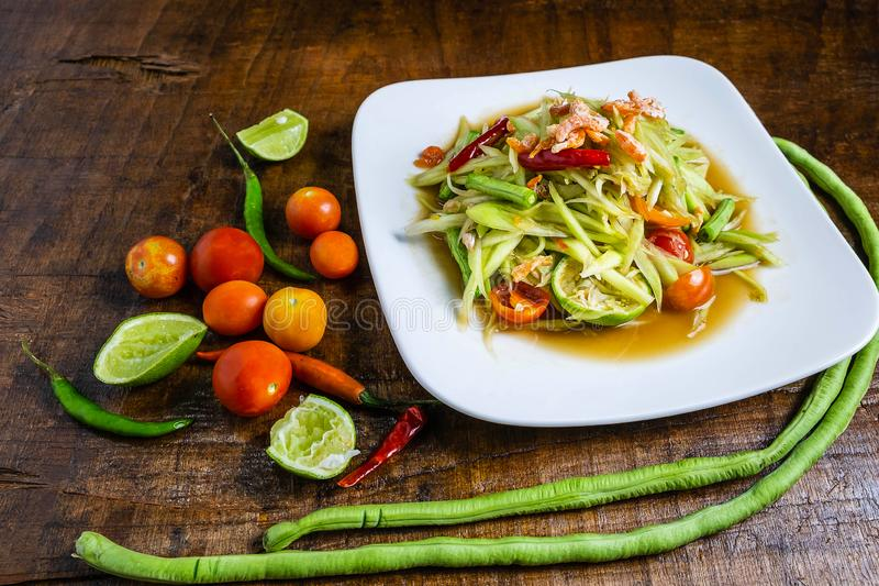 Ensalada tailandesa de la papaya de la comida en una tabla de madera imagenes de archivo