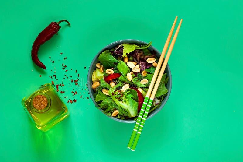 Ensalada tailandesa picante con carne de vaca y nueces en cuenco azul con los palillos en el fondo verde claro, concepto del alim fotos de archivo libres de regalías