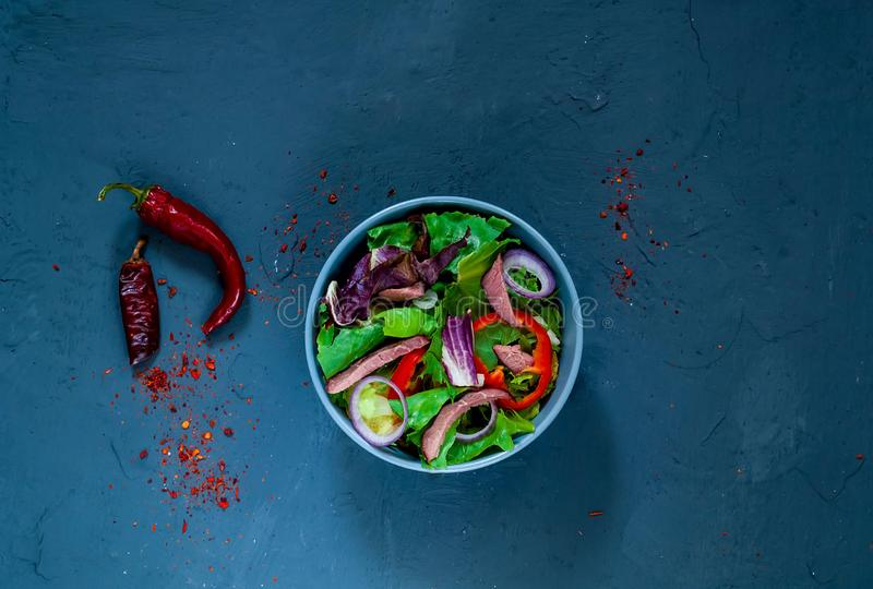 Ensalada tailandesa picante con la carne de vaca, rico sazonada con las especias selectas en cuenco azul en el fondo azul del hor foto de archivo libre de regalías