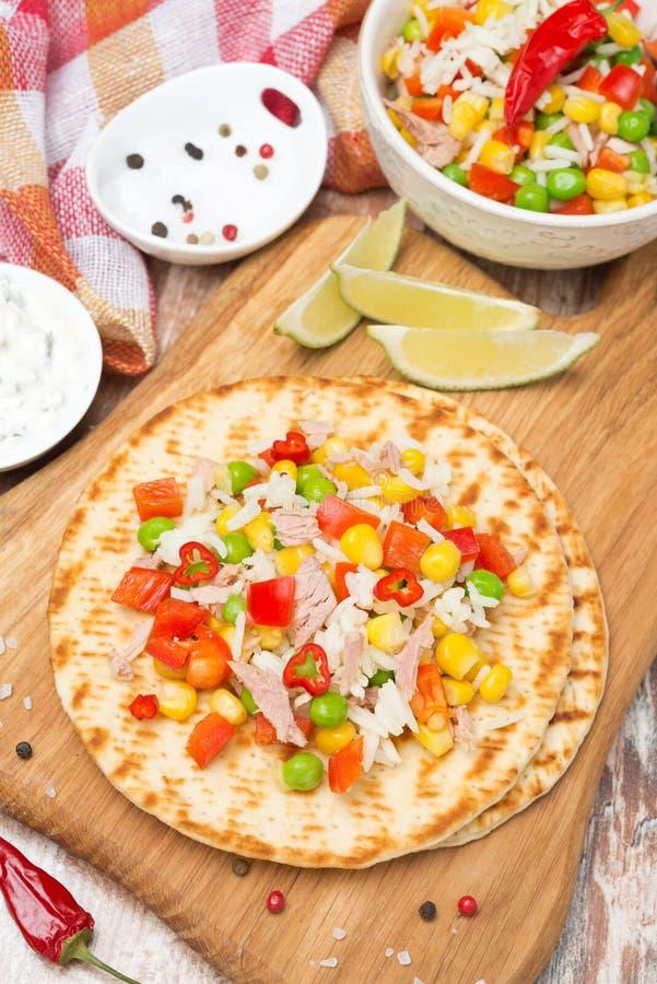 Ensalada vegetal colorida con el atún en las tortillas del trigo a bordo foto de archivo libre de regalías