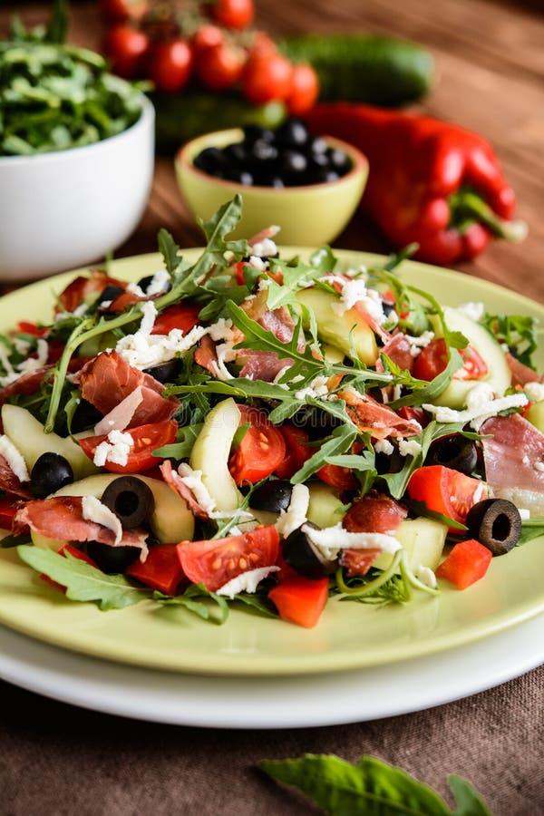 Ensalada vegetal con el jamón del bosque negro, el arugula, el pepino, las aceitunas negras, la pimienta roja, el tomate y la moz imágenes de archivo libres de regalías
