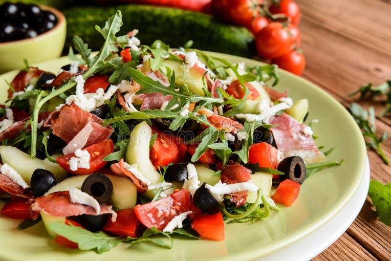 Ensalada vegetal con el jamón del bosque negro, el arugula, el pepino, las aceitunas negras, la pimienta roja, el tomate y la moz imagenes de archivo