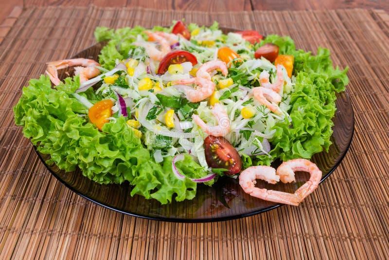 Ensalada vegetal con las colas del camarón en el primer de cristal del plato fotos de archivo