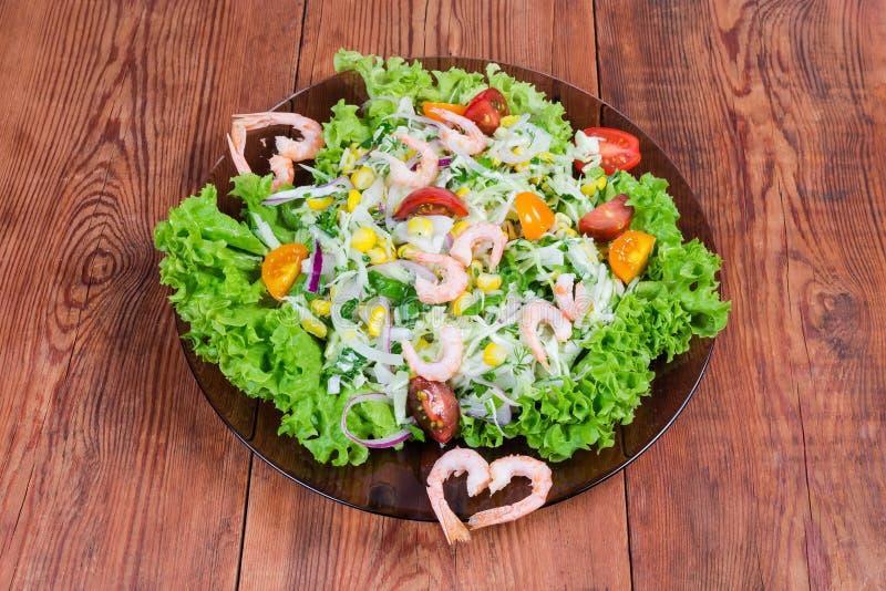 Ensalada vegetal con las colas hervidas del camarón en el plato de cristal fotos de archivo