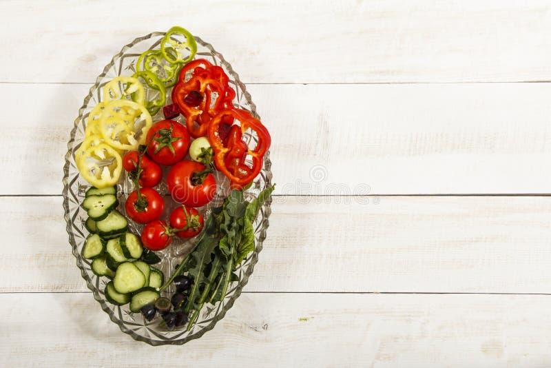 Ensalada vegetal con las verduras frescas del tamata, de pepinos, de la lechuga, de la cebolla y del arugula en una tabla de made foto de archivo libre de regalías