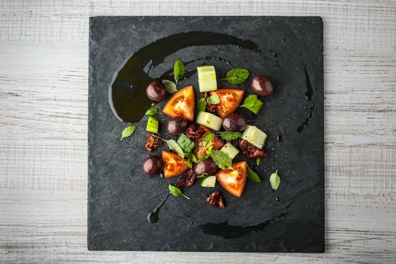 Ensalada vegetal con los tomates y la aceituna secados en la visión superior de piedra negra fotos de archivo