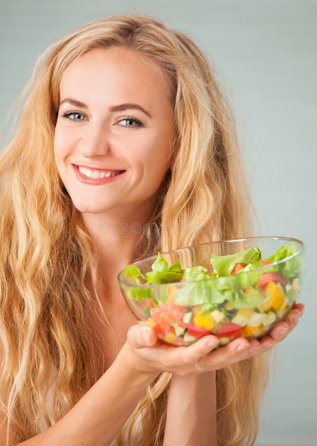 Ensalada vegetal de la consumición femenina joven fotos de archivo