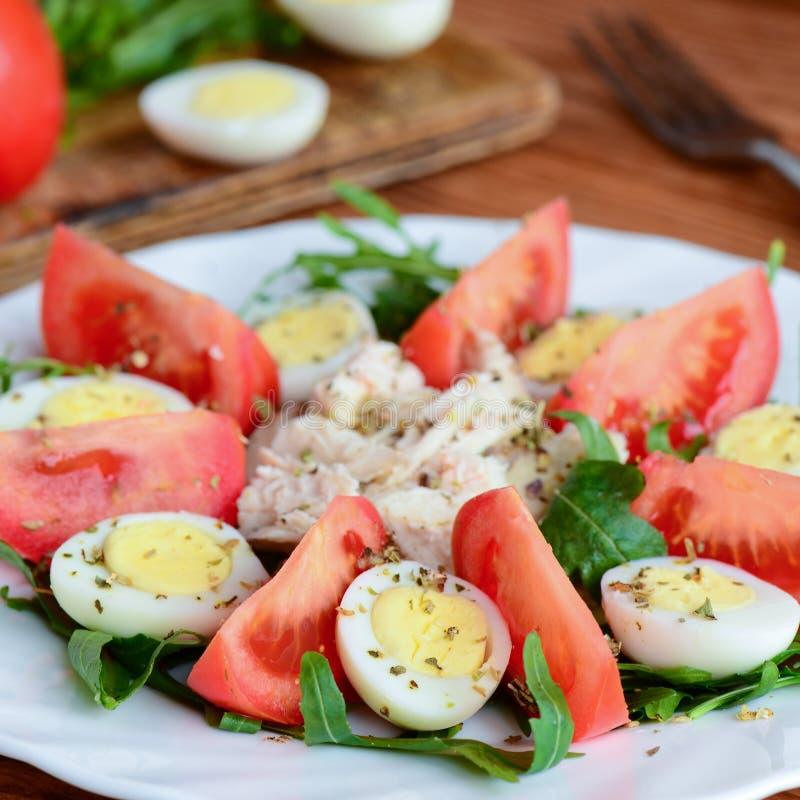 Ensalada vegetal fácil con el pollo y los huevos La ensalada con las rebanadas de los tomates, arugula, hirvió los huevos de codo fotografía de archivo libre de regalías