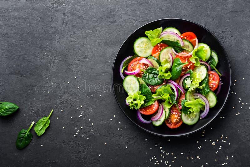 Ensalada vegetal sana del tomate, del pepino, de la cebolla, de la espinaca, de la lechuga y del sésamo frescos en la placa Menú  imagen de archivo