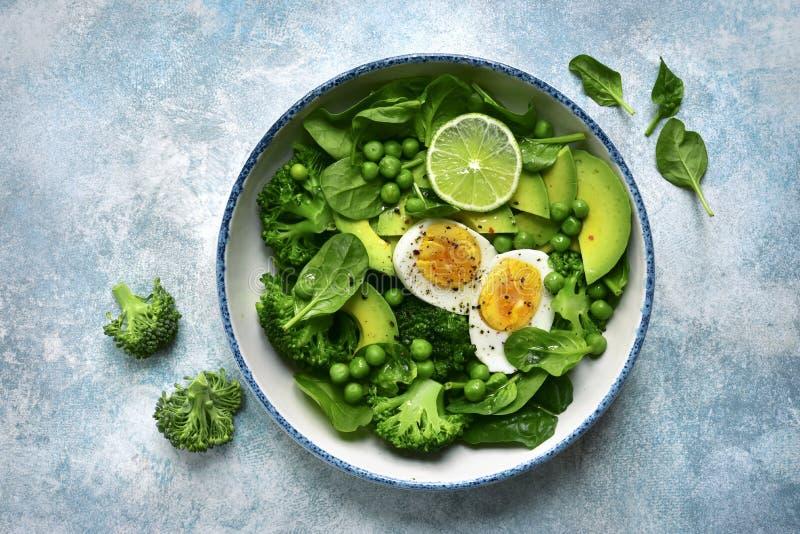 Ensalada vegetal verde con el aguacate, el bróculi, el guisante y los huevos hervidos en un fondo azul claro de la pizarra, de pi imagenes de archivo