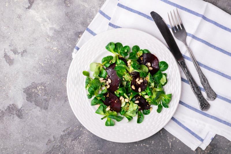 Ensalada vegetariana de las remolachas frescas de la lechuga de las verduras crudas en una placa redonda blanca en un fondo gris imagen de archivo libre de regalías