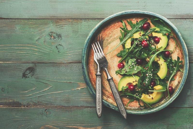 Ensalada vegetariana sana con el aguacate, el arugula, arándanos, semillas de lino y semillas de sésamo en un fondo de madera ver imagen de archivo libre de regalías