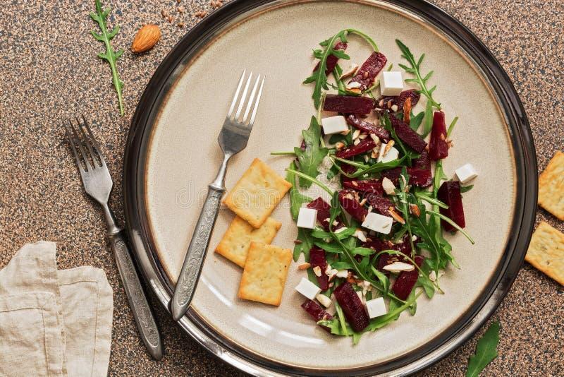 Ensalada vegetariana sana con remolachas, arugula, queso feta y galletas en un fondo de piedra marrón Visión superior imagenes de archivo