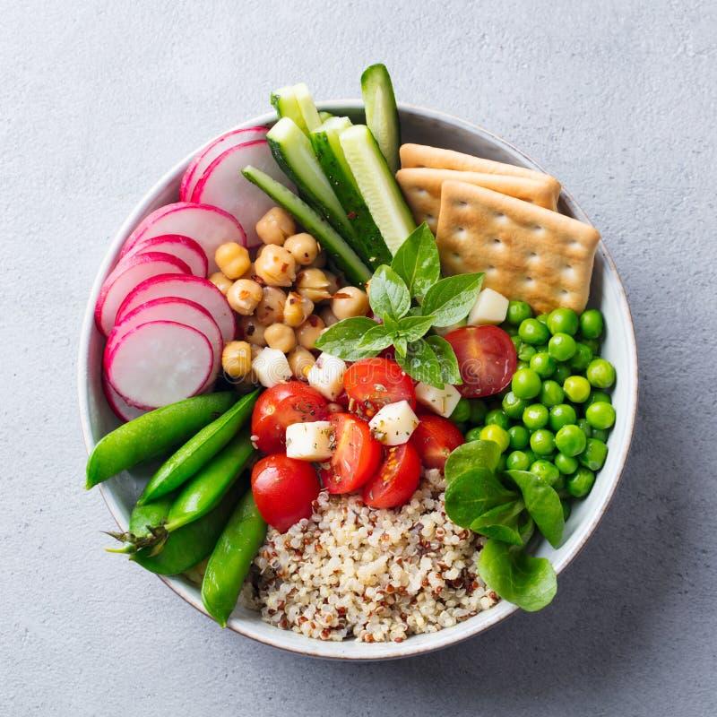 Ensalada vegetariana sana Cuenco de Buda Quinoa, garbanzo, tomates, guisante, rábano, pepino, galletas Visi?n superior fotografía de archivo