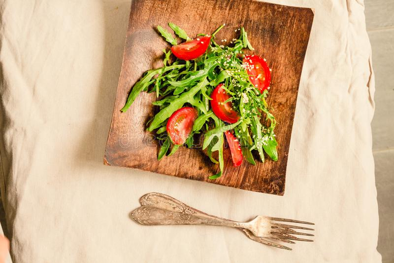 Ensalada verde clara fresca con el aguacate y los tomates en una placa de madera Visión superior fotografía de archivo