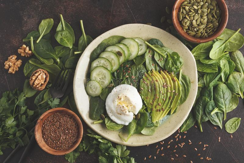 Ensalada verde con espinaca, el pepino, el aguacate, el huevo, el lino y el pumpk imágenes de archivo libres de regalías