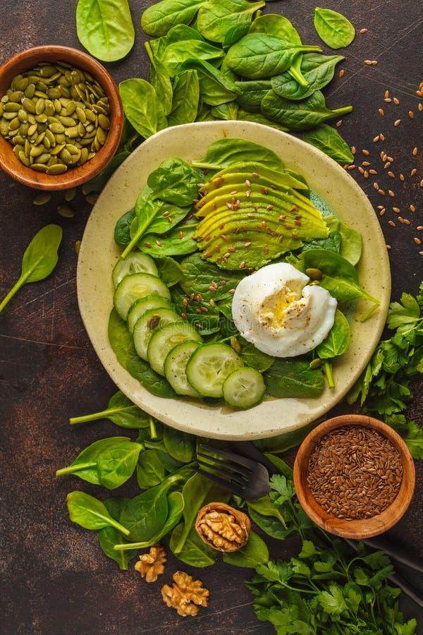 Ensalada verde con espinaca, el pepino, el aguacate, el huevo, el lino y el pumpk fotos de archivo