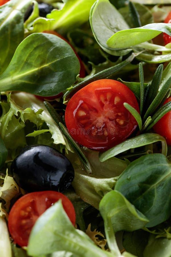 Ensalada verde con los tomates y las aceitunas negras fotos de archivo