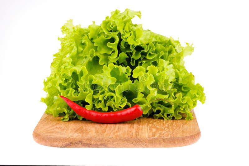 ensalada verde en un tablero de madera y las pimientas de chile en un fondo blanco foto de archivo libre de regalías