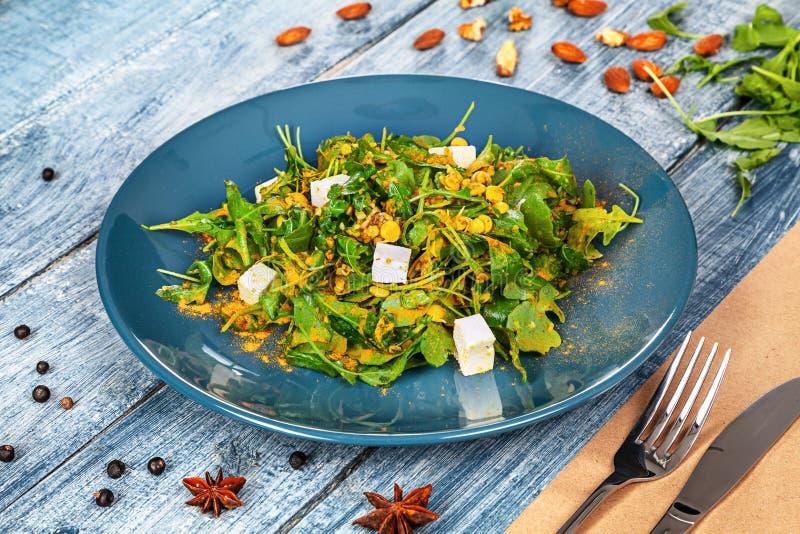 Ensalada verde fresca del vegano servida en placa azul en fondo de madera azul con los ingridents espinaca, garbanzo, queso Alime imágenes de archivo libres de regalías