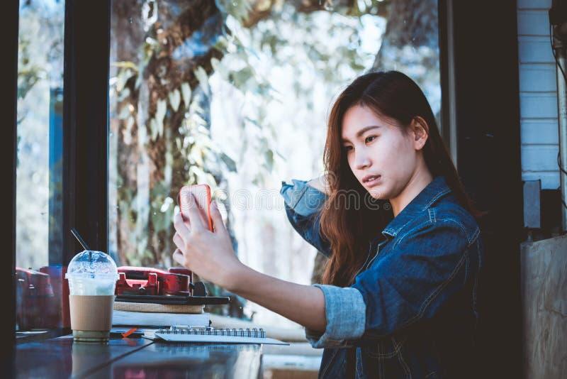 Ensam användande mobiltelefon Asien för tonårs- sammanträde med selfie i kafé arkivfoton