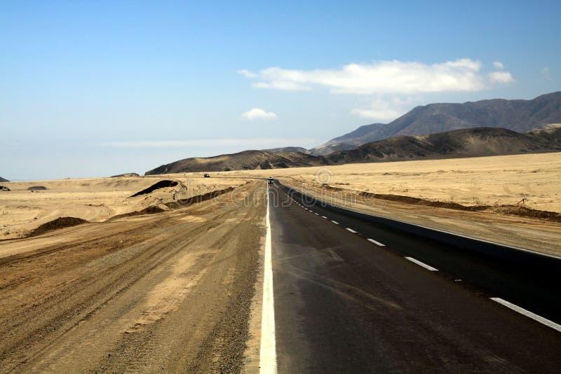 Ensam asfaltväg till och med kargt förlorat land in i endlessness av den Atacama öknen, Chile arkivfoton