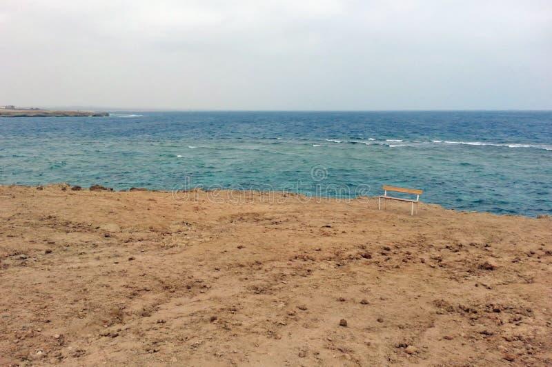 Ensam bänk på stranden, Egypten, Marsa Alam, Röda havet royaltyfria bilder