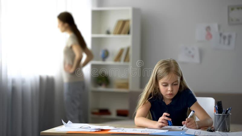 Ensam barnteckningsbild, strikt moderanseende vid fönstret, spänd atmosfär royaltyfria bilder
