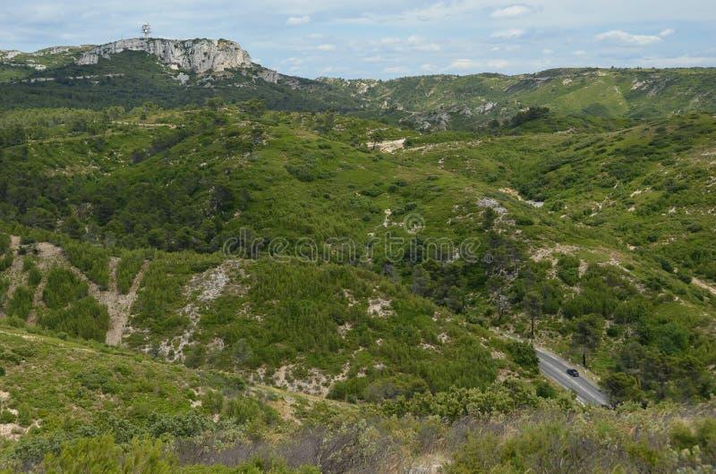Ensam bil på en väg som leder till och med Provencal berg arkivbild