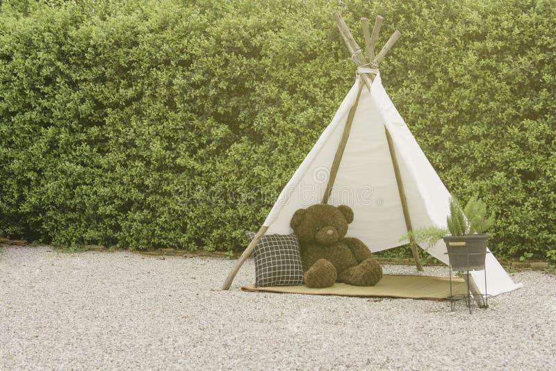Ensam björndocka i tipin, indiskt tält i trädgården, tappningstil royaltyfri foto