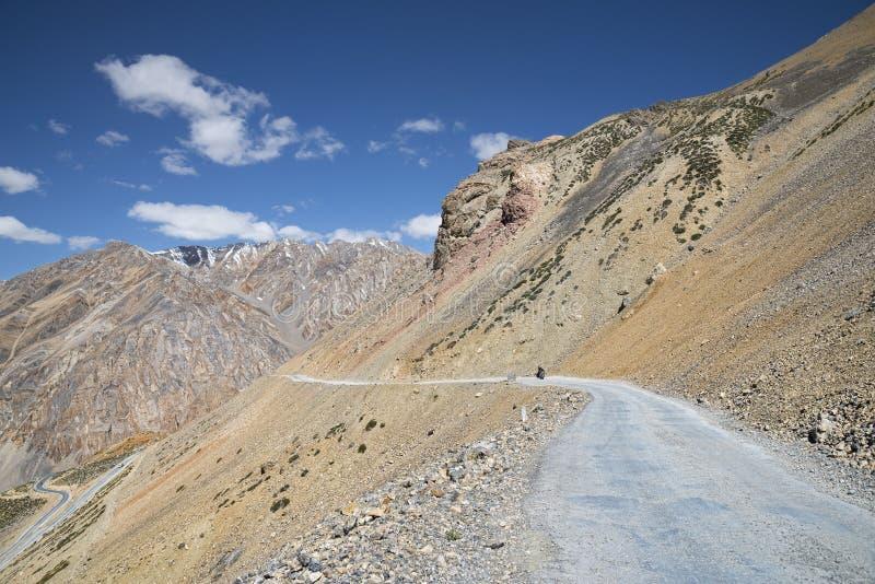 Ensam cyklist på bergvägen royaltyfria bilder