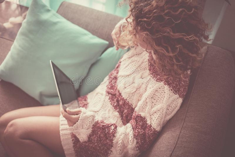 Ensam dam som är hemmastadd med den hållande ögonen på teknologiminnestavlan för lockigt brunt hår förbindelse till internet för  arkivfoto