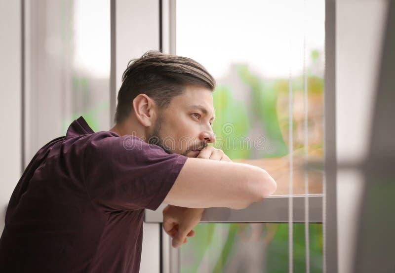 Ensam deprimerad man nära fönster arkivbild
