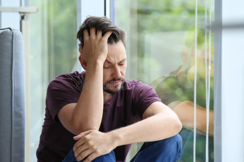 Ensam deprimerad man nära fönster arkivfoto