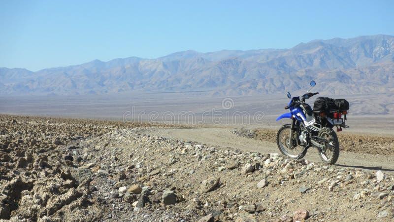 Ensam dubbelsportmotorcykel på den tomma grusvägen i den Death Valley öknen i Förenta staterna arkivbild