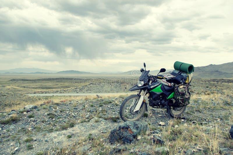 Ensam endurohandelsresande för motorcykel med resväskor på stenöknen royaltyfria foton