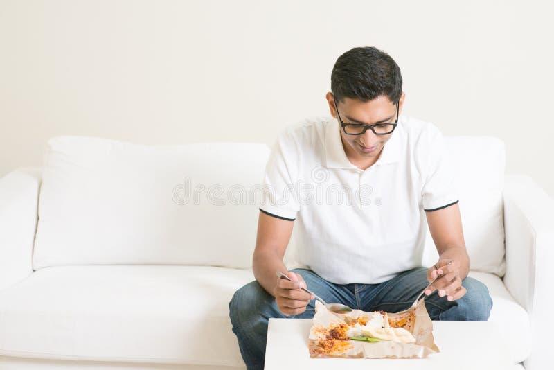 Ensam enkel man som hemma äter mat bara royaltyfri foto